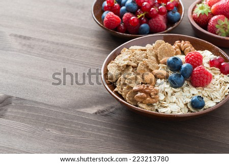 oatmeal, granola, nuts and berries on wooden background and place for text, horizontal - stock photo