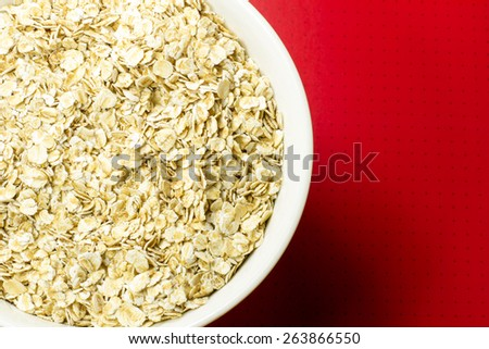 oatmeal in a bowl on red background - stock photo