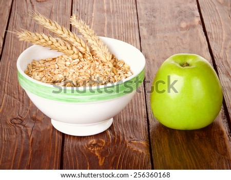 oatmeal in a bowl with cones and green apple on a wooden table - stock photo