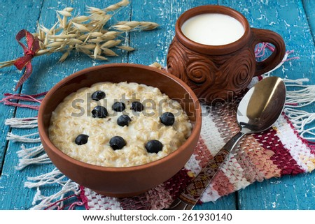 Oatmeal in a clay bowl, milk mug, homespun mat, stalks of oats on a blue wooden background - stock photo