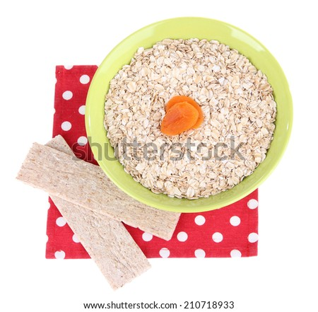 Oatmeal in a green bowl with dried apricots and crisp bread on a red polka dot napkin isolated on white