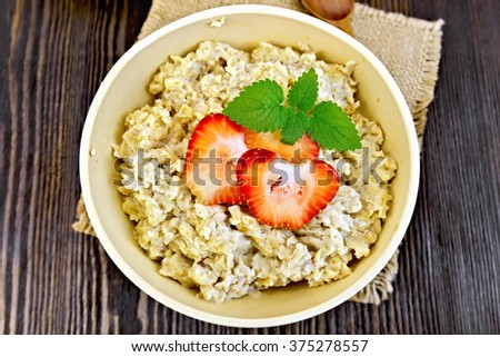 Oatmeal in a yellow cup with strawberries on a napkin of burlap, spoon on dark background board