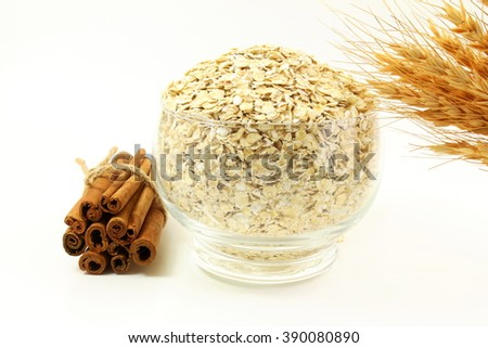 oatmeal in bowl with cinnamon and oats ears on white background