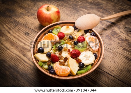 Oatmeal in bowl with fruits on old wooden table - stock photo