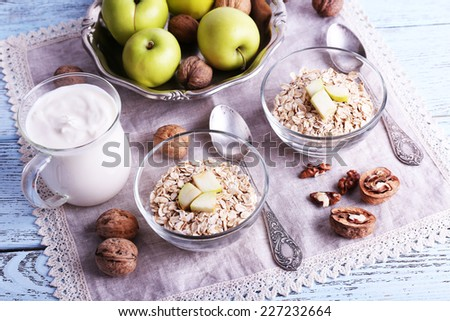 Oatmeal in bowls, walnuts, apples and yogurt on napkin on blue wooden background - stock photo