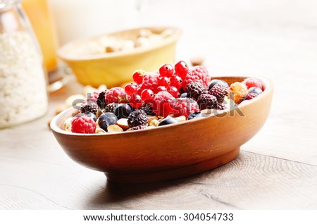 Oatmeal oats with berries nuts orange juice and yogurt on wooden table