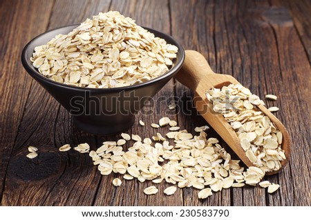 Oatmeal or oat flakes in bowl and scoop on dark wooden table  - stock photo