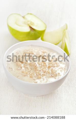 Oatmeal porridge and apple slices  - stock photo