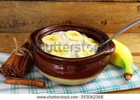 oatmeal porridge in bowl topping with banana - stock photo