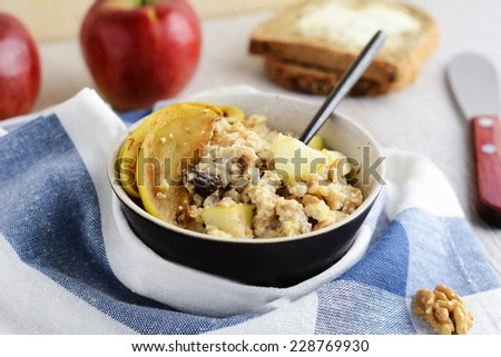 Oatmeal porridge in bowl with caramelized apples, raisins and walnuts. Whole wheat toasts with butter and apples on background - stock photo