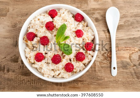 Oatmeal porridge in bowl with raspberries on wooden table. Healthy food for breakfast. Top view - stock photo