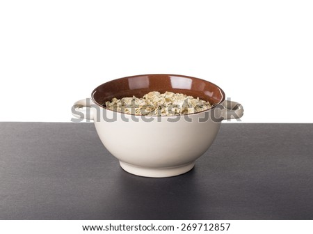 Oatmeal porridge in ceramic drinking bowl. Located on yellow table.