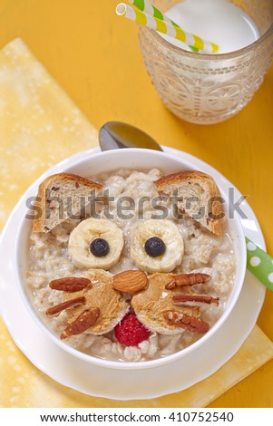 Oatmeal porridge with a kitten face decoration - stock photo