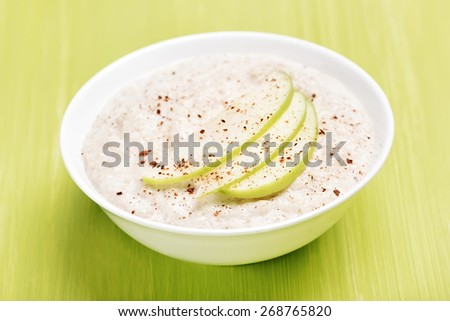 Oatmeal porridge with apple slices and cinnamon in white bowl, shallow depth of field - stock photo