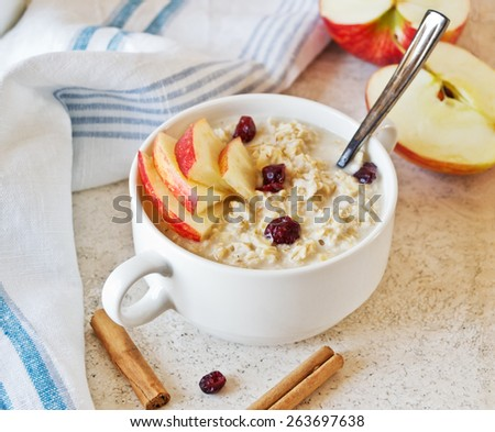 Oatmeal porridge with apples and cinnamon on marble table - stock photo