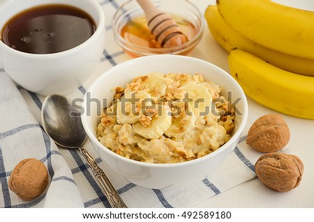 Oatmeal porridge with banana, honey and walnuts, selective focus
