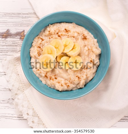 Oatmeal porridge with banana slices and cinnamon over white wooden table. Selective focus - stock photo