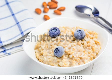Oatmeal porridge with blueberries and almonds on white table, close up of healthy dietary breakfast - stock photo