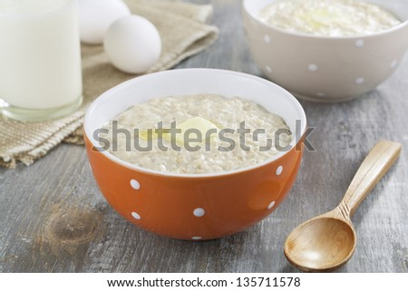 Oatmeal porridge with butter, milk and eggs on a wooden table