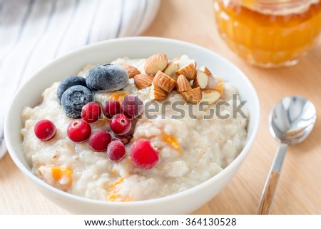 Oatmeal porridge with dried apricots, blueberries, cranberries and chopped almonds on bright wooden table. Jar of honey on background. Selective focus. Bright healthy breakfast image. Close up - stock photo