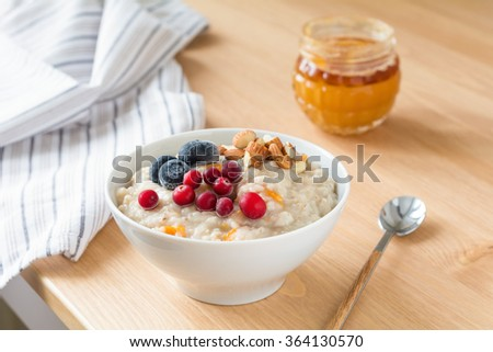 Oatmeal porridge with dried apricots, blueberries, cranberries and chopped almonds on bright wooden table. Jar of honey on background. Selective focus. Bright healthy breakfast image - stock photo