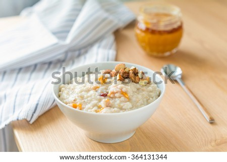 Oatmeal porridge with dried fruits, honey and nuts in bowl on breakfast table - stock photo
