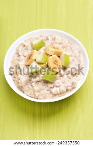 Oatmeal porridge with fruit slices in white bowl, top view - stock photo