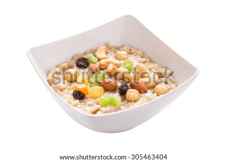 Oatmeal porridge with nuts and fruits in bowl isolated on white background - stock photo