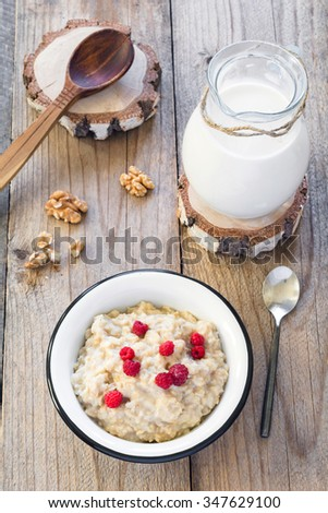 Oatmeal porridge with raspberries and milk on textured wooden table, country style healthy breakfast. Top view, vertical composition - stock photo