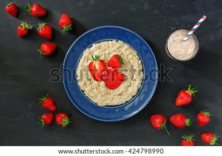 Oatmeal porridge with strawberries in vintage blue plate on a dark surface with ice cream milkshake, top view. Healthy breakfast - stock photo