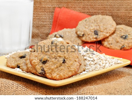 Oatmeal raisin cookies with a glass of milk.  Burlap background, close up.