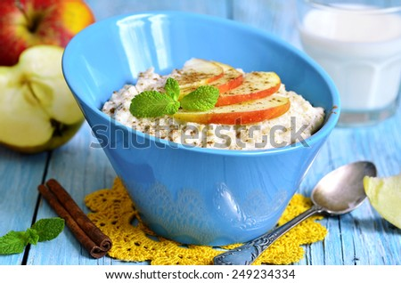 Oatmeal with apple and cinnamon on a blue wooden table. - stock photo