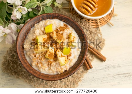 Oatmeal with apple, honey and cinnamon in the bowl and cinnamon sticks on the wooden board  - stock photo