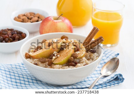 oatmeal with apples, raisins and cinnamon for breakfast, close-up