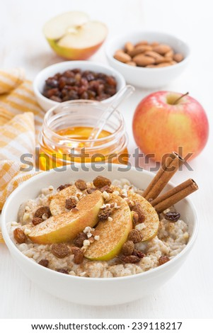 oatmeal with apples, raisins, cinnamon and ingredients on white wooden table, vertical, top view