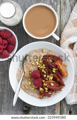 oatmeal with baked fruit, fresh coffee with milk on wooden background, closeup top view - stock photo