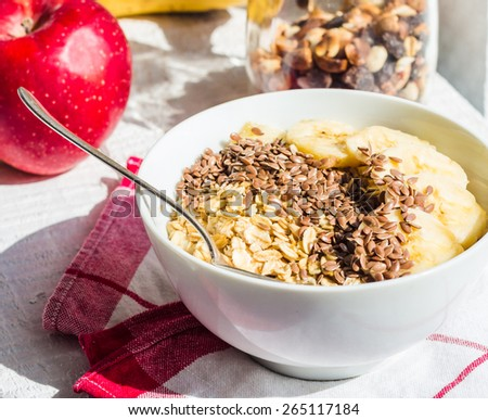 oatmeal with banana and flax seeds, apples, nuts and dried fruit jar, a healthy breakfast - stock photo