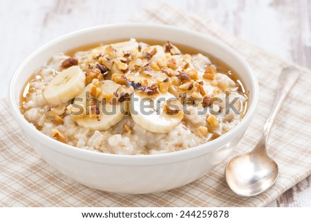 oatmeal with banana, honey and walnuts in bowl for breakfast - stock photo
