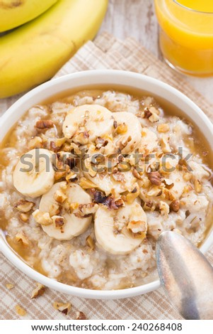 oatmeal with banana, honey and walnuts in bowl for breakfast, top view, close-up, horizontal - stock photo
