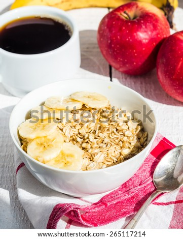oatmeal with bananas, apples and a cup of coffee, a healthy breakfast - stock photo