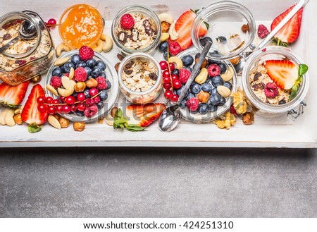 Oatmeal with berries and nuts in glass jars, top view. Healthy breakfast , sports nutrition or diet food concept - stock photo