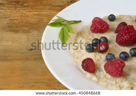 Oatmeal with  berries (raspberry, wild strawberry, blueberry) in white plate decorated with green leaf on wooden background