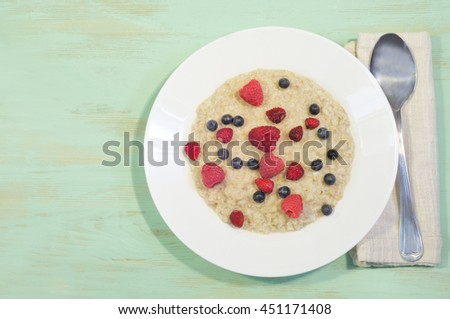 Oatmeal with  berries (raspberry, wild strawberry, blueberry) in white plate on wooden table. Overhead view. Image has copyspace for your text