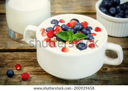 oatmeal with blueberries and strawberries in the white bowl on a dark wood background. toning. selective focus on mint