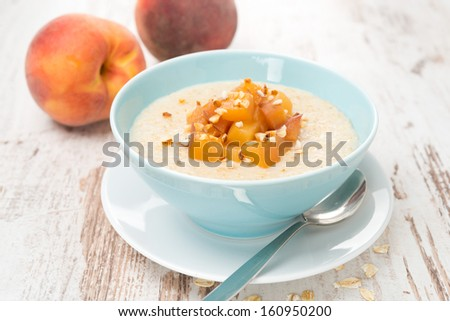 oatmeal with caramelized peaches in a bowl for breakfast, horizontal - stock photo