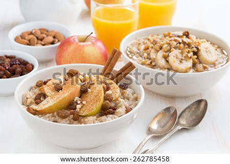 oatmeal with fresh apples, raisins and cinnamon for breakfast on white table, close-up - stock photo