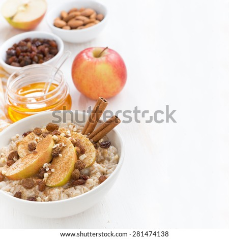 oatmeal with fresh apples, raisins, cinnamon and ingredients on white wooden background, close-up