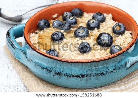 Oatmeal with fresh blueberries drizzled with honey over a rustic wooden background.