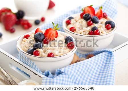 Oatmeal with fresh fruits and honey in small bowls on tray. - stock photo