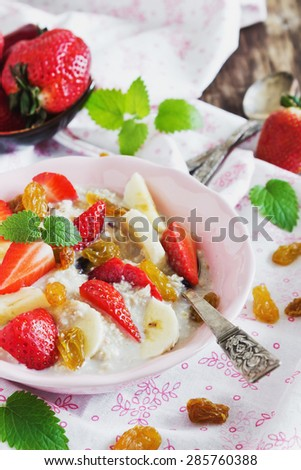 oatmeal with fresh strawberries, banana and raisins on the table. close-up.health or cooking concept. selective focus
